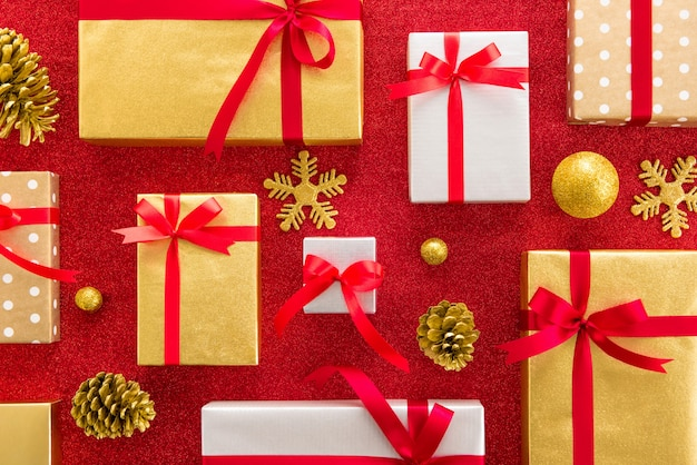 Conjunto de caixas de presente brilhante com artigos de decoração em fundo vermelho brilhante