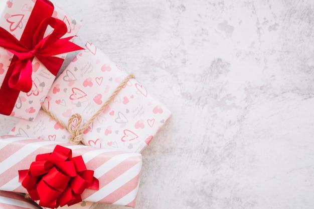 Conjunto de caixas de presentes no envoltório com fita vermelha, arco e torção
