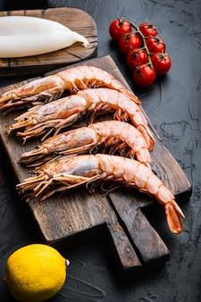 Conjunto de camarão rei com ingredientes para paella na superfície de concreto preto, foto de comida.