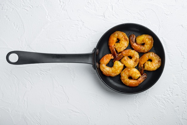 Conjunto de camarões grelhados, em frigideira de ferro, em branco