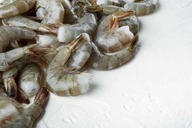 Conjunto de camarões tigre ou camarões tigre asiático, em uma superfície de pedra branca, com espaço de cópia para o texto