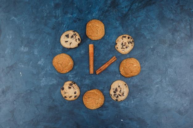Conjunto de canela e diferentes tipos de cookies em um fundo azul escuro. colocação plana.