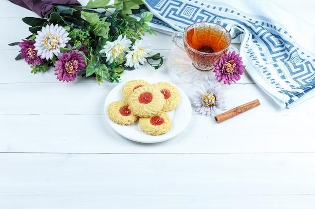 Conjunto de canela, xícara de chá, pano de prato e biscoitos, flores sobre fundo branco placa de madeira. vista de alto ângulo.