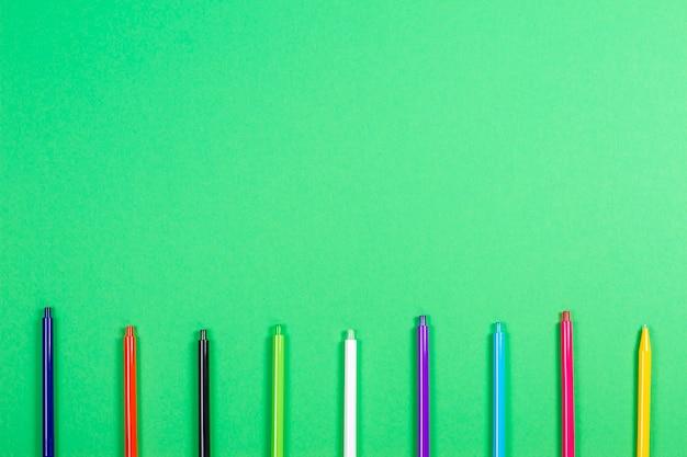 Conjunto de canetas coloridas sobre fundo verde