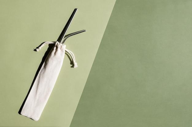 Conjunto de canudos de aço reutilizáveis de cor metálica em fundo verde conceito de estilo de vida sustentável ...