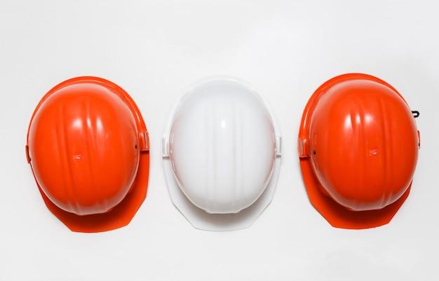Conjunto de capacetes. dois laranja e um branco.