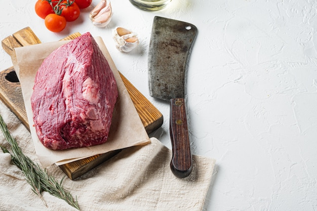 Conjunto de carne bovina de peito crua, em uma tábua de madeira com uma velha faca de cutelo de açougueiro