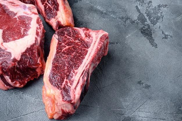 Conjunto de carne de bovino crua envelhecida a seco, tomahawk, osso t ou porterhouse e bife de clube, em fundo de pedra cinza, com espaço de cópia para o texto