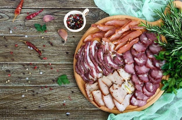 Conjunto de carne grande. linguiça caseira defumada, bacon salgado, fatias picadas basturma em uma placa de madeira com especiarias e ervas. postura plana. a vista de cima