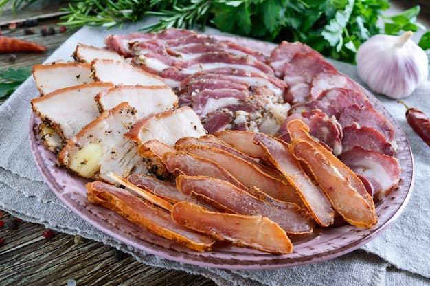Conjunto de carne grande. linguiça caseira defumada, bacon salgado, fatias picadas basturma em uma placa de madeira com especiarias e ervas.
