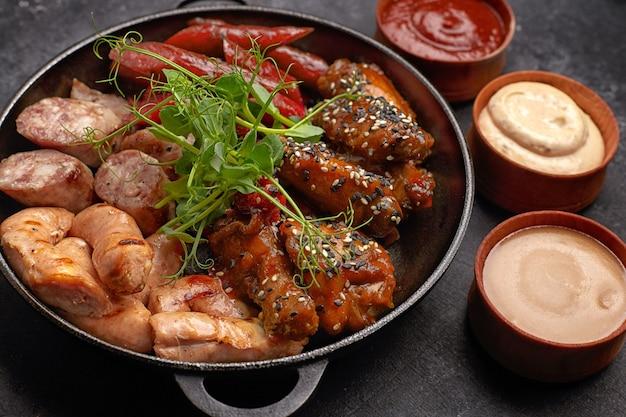 Conjunto de carne, salsicha, costela, asas grelhadas e três molhos no preto