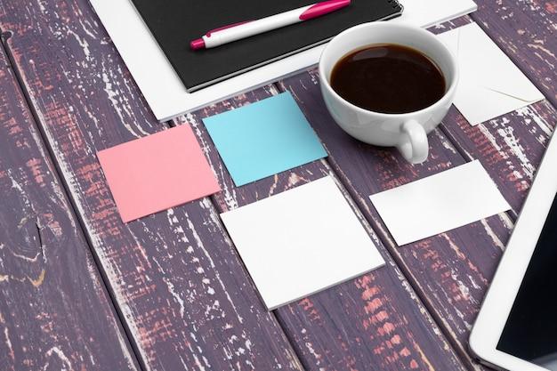 Conjunto de cartões de visita em branco, caderno e xícara de café.