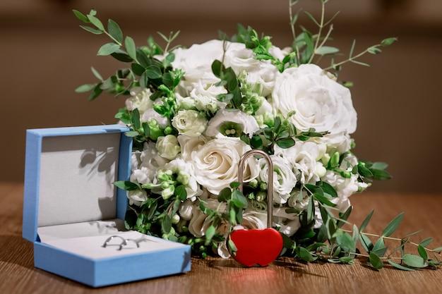 Conjunto de casamento com buquê de noiva, anéis e cadeado vermelho