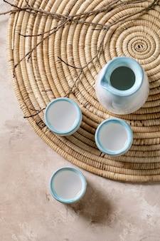 Conjunto de cerâmica de saquê para bebida alcoólica japonesa tradicional saquê de vinho de arroz, jarra e três xícaras, em um guardanapo de palha com galhos secos.