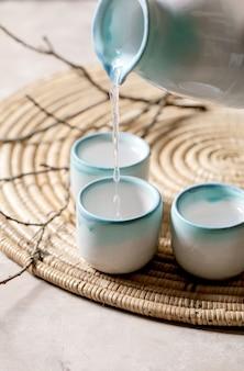 Conjunto de cerâmica de saquê para bebida alcoólica japonesa tradicional saquê de vinho de arroz servindo de uma jarra em três xícaras, em um guardanapo de palha com ramos secos