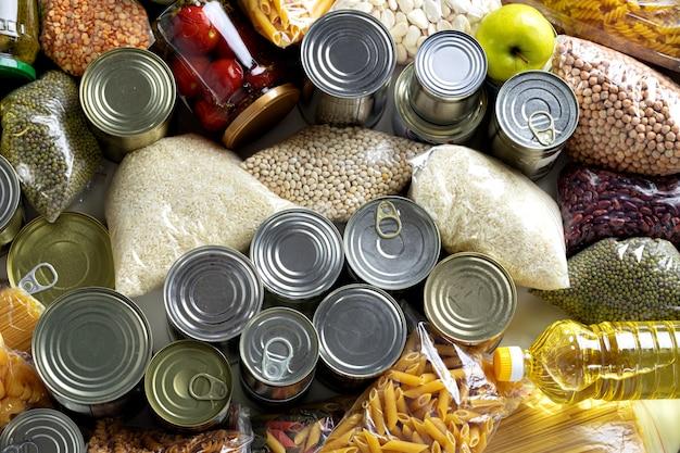 Conjunto de cereais crus, grãos, massas e alimentos enlatados em cima da mesa.