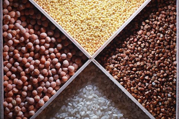 Conjunto de cereais de grãos trigo sarraceno e sêmolas de milho em uma bandeja de madeira a