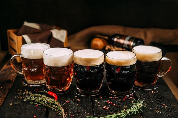 Conjunto de cerveja escura e gengibre em canecas no fundo de madeira com ervas e pimenta