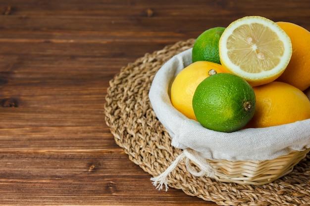 Conjunto de cesto cheio de limão e meio limão e limão sobre uma superfície de madeira. vista de alto ângulo.