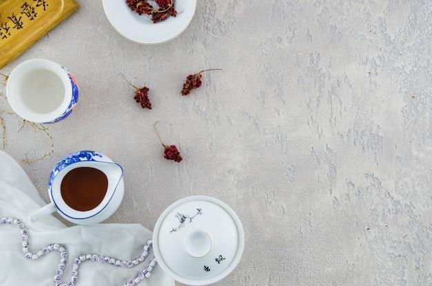 Conjunto de chá de porcelana chinesa azul e branco com ervas no pano de fundo cinzento concreto