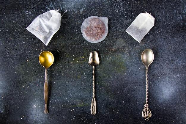 Conjunto de chá nas colheres de talheres antigos, vários tipos de chá e saquinhos de chá