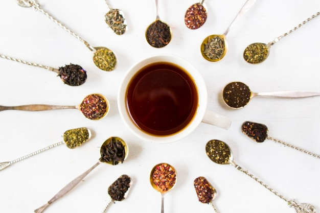 Conjunto de chá nas colheres de talheres vintage, vários tipos de chá e xícara de chá