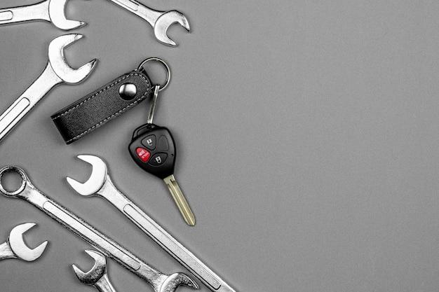 Conjunto de chave inglesa e uma chave de carro com controle remoto no chão. manutenção e cuidados antes de viajar.