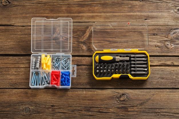 Conjunto de chaves de fenda e parafusos em superfície de madeira escura
