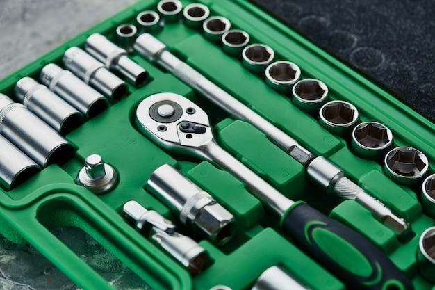 Conjunto de chaves inglesas com catraca na caixa de ferramentas de plástico verde, closeup. chave de cromo vanádio, kit de ferramentas profissional, instrumento de reparo para serviço automotivo