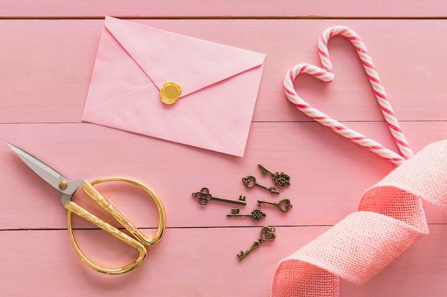 Conjunto de chaves perto de envelope, tesoura e bastões de doces