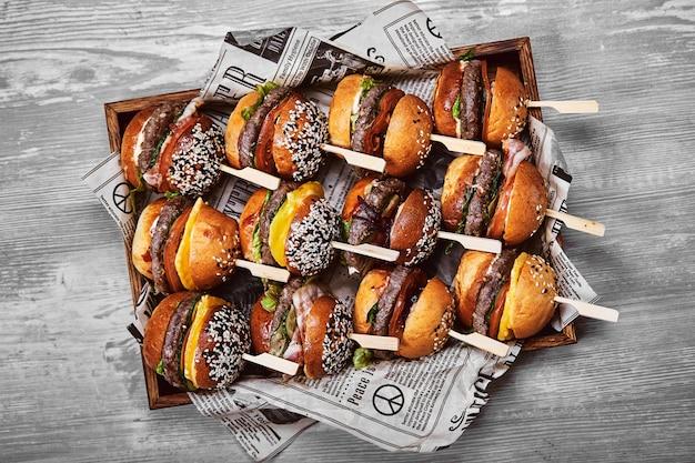 Conjunto de cheeseburger saboroso em uma caixa de madeira sobre um fundo claro. uma caixa com hambúrgueres diferentes, uma oferta definida para uma empresa,