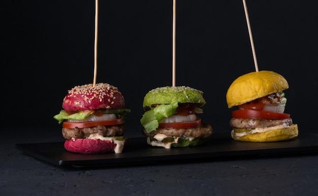 Conjunto de cheeseburgers de cores variadas em uma chapa plana em um fundo preto