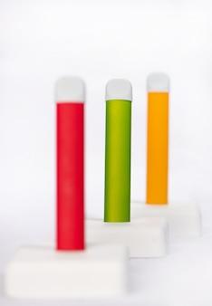 Conjunto de cigarros eletrônicos descartáveis coloridos em um expositor branco
