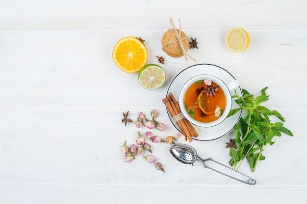 Conjunto de coador de chá, ervas, frutas cítricas, chá de ervas e biscoitos em uma superfície branca