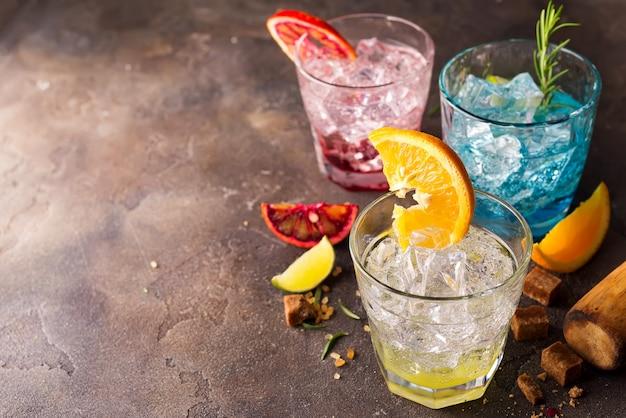 Conjunto de cocktails coloridos com frutas e ervas, açúcar mascavo em fundo de pedra