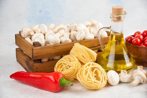 Conjunto de cogumelos, azeite de oliva extra virgem, massas, tomate cereja e pimenta em um pedaço de mármore.