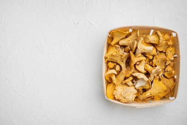 Conjunto de cogumelos chanterelle, em caixa de madeira, no fundo da mesa de pedra branca, vista superior plana, com espaço de cópia para o texto