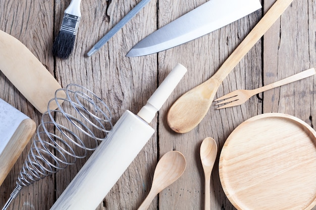 Conjunto de colher de pau e faca no fundo da velha mesa de madeira