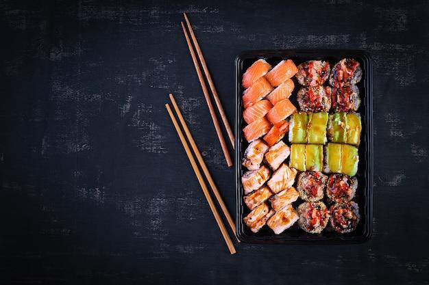 Conjunto de comida asiática. sushi, rolos em um fundo preto. vista superior, acima