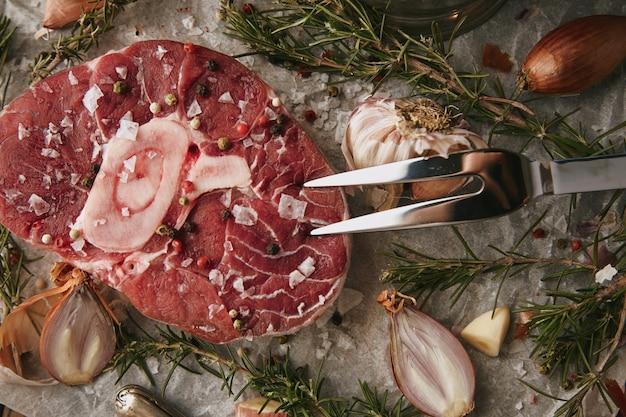 Conjunto de comida, cebola, romero, bife de carne crua, sal, pimenta, alho, azeite, garfo. close up, vista de cima