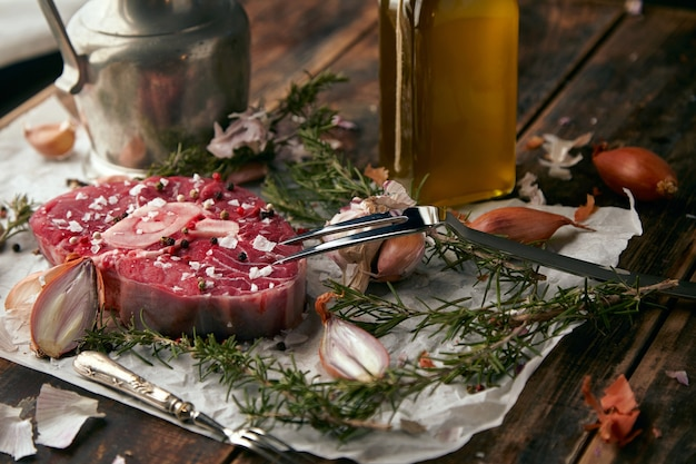 Conjunto de comida, cebola, romero, bife de carne, sal, pimenta, alho, azeite, garfo