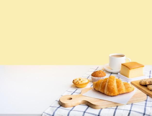Conjunto de comida de café da manhã ou padaria, bolo na mesa da cozinha com fundo de espaço de cópia