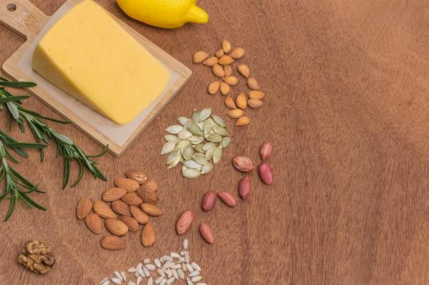 Conjunto de comida saudável com queijo, amêndoas, sementes de girassol, nozes, amendoim, sementes de abóbora