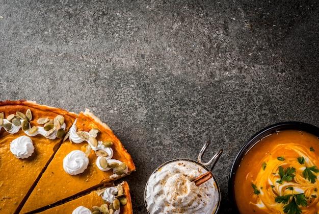 Conjunto de comida tradicional de outono. dia das bruxas, ação de graças. latte de abóbora picante, torta de abóbora e tartaletes com chantilly e sementes de abóbora, sopa de abóbora, na mesa de pedra preta. vista superior do espaço da cópia