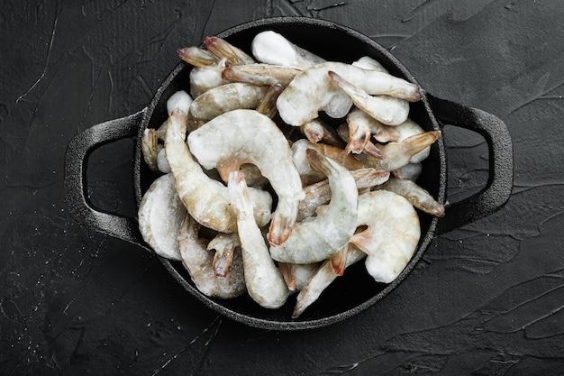 Conjunto de conchas congeladas em camarões tigre ou camarões tigre asiáticos, em frigideira de ferro fundido, em mesa de pedra preta, vista de cima plano plano