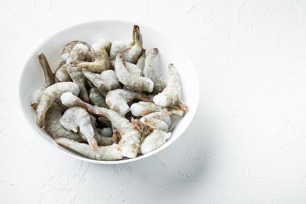 Conjunto de conchas congeladas em camarões tigre ou camarões tigre asiáticos, em superfície de pedra branca, com espaço de cópia para o texto