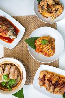Conjunto de configuração de menu popular de frutos do mar tailandeses na mesa branca.
