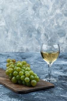 Conjunto de copo de vinho e uvas brancas em uma placa de corte em um fundo de mármore azul claro e escuro. fechar-se.