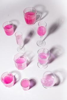 Conjunto de copos com água de rosas em um fundo branco.
