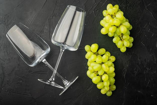 Conjunto de copos de vinho com uvas, mesa de pedra preta, vista de cima plana
